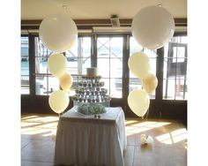 Ivory and white balloons topped with a stunning 3ft balloon - perfect addition to a cake table #ivory #white #balloons #giantballoons #caketable