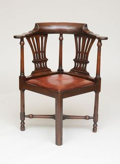 GEORGE III MAHOGANY CORNER ARMCHAIR -   The curved top rail above the pierced back splats with alternating columnar supports, above the drop seat and conforming apron, raised on turned legs, joined by an X-formed stretcher, ending in double bun feet. 33 x 28 1/4 x 25 3/4 in.    Provenance: Reindeer Antiques, Ltd., Northamptonshire, England, 1987.
