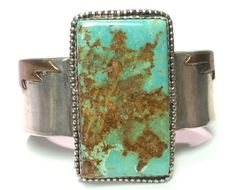 This sterling silver cuff is hefty and makes a statement! The bracelet features a very large piece of rectangular turquoise. The color is very