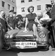 Italian actress Sophia Loren on the hood of a car at the Rally of Cinema III Rome 1956