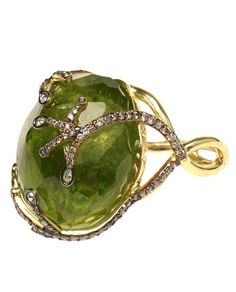 A large faceted green peridot artfully set in an 18K yellow gold ring by Kimberly McDonald . 154 carats  18K yellow gold  Champagne and brown diamonds