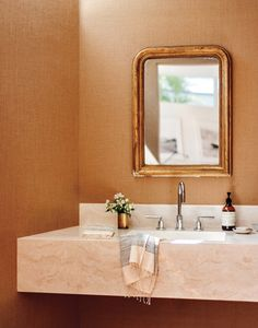 Travertine stone with hints of gold practically glow against the textured wallpaper and metallic mirror.