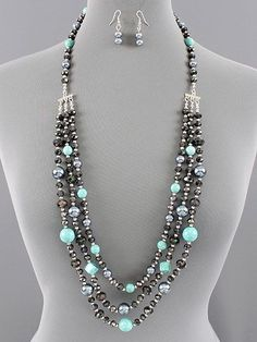 Beautiful triple layered beaded necklace with Turquoise dyed Howlite gems, grey pearls and black faceted crystals.  Beads range from about 6mm-14mm.  Pretty silver stations take this multi strand down to one for easy on and off over the neckline.  Tons of beads on this and tons of sparkle!  This ...: