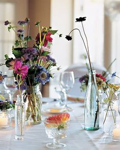 Locally grown flowers made up the centerpiece for each table. For vases, Wendy used her mother's collection of vintage canning jars and added bottles gathered from antiques stores, thrift shops, and flea markets. Wildflower Centerpieces, Glass Centerpieces, Wedding Reception Decorations, Table Decorations, Reception Ideas, Wedding Glasses, Vintage Bottles, Martha Stewart Weddings, Different Flowers
