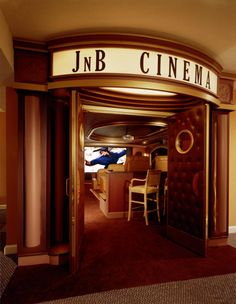 Love the entrance to this home theatre + the bar chairs at the back