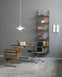 Pendant lighting, shelving behind or beside workspace/desk. Grey wall.