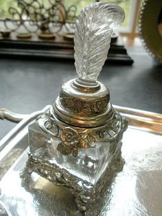 This crystal inkwell with a plum top sits within a pewter stand.    a pewter stand.