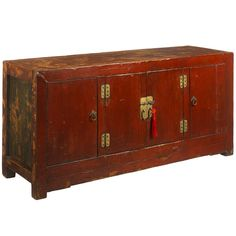 A beautiful, deep red lacquer sideboard from Qinghai province in western China, dating from around 1900. The shape and design are almost modern, with thick frames and minimal decoration. The two side doors have been added recently in place of what would originally have been fixed panels, making the cabinet more practical for use as a modern sideboard.