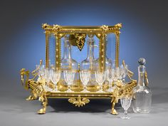 This important Baccarat cavé liqueur was created in the same year Baccarat registered its first mark. Four etched Baccarat decanters and twelve matching cordial glasses are housed in their beautiful glass and doré bronze enclosure, which features an exotic dragon, bamboo and lotus blossom motif.brbrCirca 1860