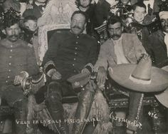 Pancho Villa and Emiliano Zapata, Decembre 6th, 1914. General Villa is sitting on the official presidential chair.  This would be like if George Washington had gone and sat on the king's throne.