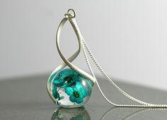 """Eine besondere Halskette, die ganz klassisch im Ausschnitt getragen wird. Echte Vergißmeinnicht eingegossen in einer Kugel. Diese """"schwebt"""" in einer mattierten versilberten Spiralfassung, die..."""