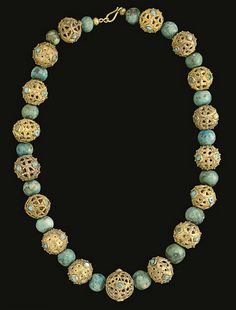 A MIDDLE BYZANTINE OR ISLAMIC GOLD BEAD NECKLACE   CIRCA 8TH-9TH CENTURY A.D.   With seventeen beads composed of gold sheet cut out to form a openwork designs embellished by filigree and granulation, some with circles with cruciform motifs and some with circles within circles, round and oval bezels vertically between, now set with turquoise and blue glass, interspersed with turquoise beads; strung with a modern hook-and-loop closure