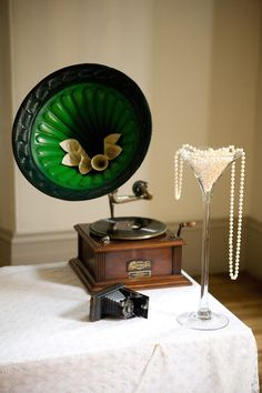 pearl dripping from champagne glass 1920's wedding style Downton Abbey wedding http://www.blushrose.co.uk/manchester-wedding-florist/ Great Gatsby 1920's wedding ideas themes pearls dripping. Pearl wedding theme vintage gramophone adds a glamorous vintage theme for your wedding