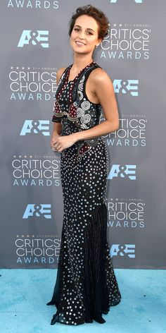ALICIA VIKANDER wears a custom Mary Katrantzou gown with multiple types of heavy beading and a messy, backswept updo with tiny drop earrings.
