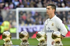 Cristiano Ronaldo poses with his four Ballon d'Or France Football trophies at the Santiago Bernabeu stadium in Madrid.