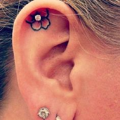 Flower ear tattoo with a stud in the middle - Nice idea and you can try on different colored studs to make your tattoo look better.