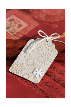 Die cut tags or embellishments using gesso to create letterpress effect. Washes off the folder with soap and water.