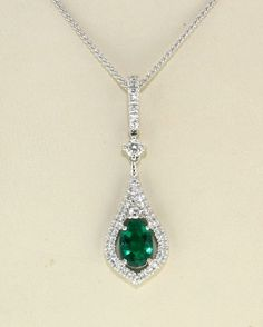 18Kt. white gold drop design emerald and diamond pendant, set with 1 @ Oval faceted Natural Emerald, 0.50cts. in weight and 39 round diamonds with a total weight of 0.27 cts.