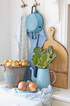A Corner of the Kitchen ~ Aluminium Pail of Potatoes, Enamel Coffee Pot with Rhubarb Leaves, Onions in a Dish, Enamel Colander & Cloths hanging on Hooks, and Wooden Chopping Board