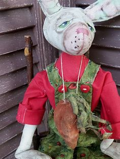 16 tall, Mr. Fudd, wears a red shirt with green floral heart print bib overalls.  He has a detailed head with separately stitched on eyelids and painted snout and wired ears that have faint green polka dots and posable. Heart buttons hold his trousers up, and he wears a 3 long carrot around his neck in case he wants a snack. It has been signed/dated as an original, one of a kind collectible design which is not a toy nor intended for childrens use or play.  Thanks for stopping to view thi...