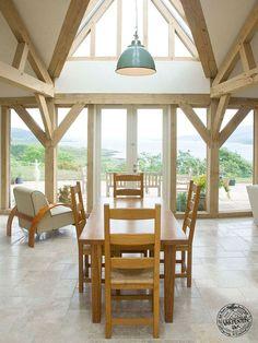 Completely bespoke design with up-turned-boat-inspired-shard-roof-light creates light and airy oak frame house. Hand crafted in Carpenter Oak's Devon workshops.