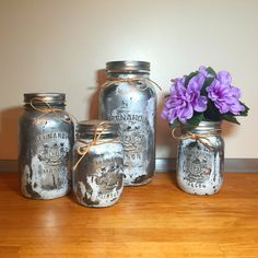 """This distressed silver 4 piece painted mason jar kitchen gift set, complete with flower vase, adds the perfect rustic charm to your kitchen. Our unique colours add a gorgeous pop of colour to your home and pull their weight when organizing your kitchen items. The lids are covered in a beautiful jute/burlap fabric.     PLUS: Short on time? Choose to receive the set pre-gift wrapped! Just select """"gift wrapped"""" in the drop down menu. No other mason jar listing includes this much value…"""
