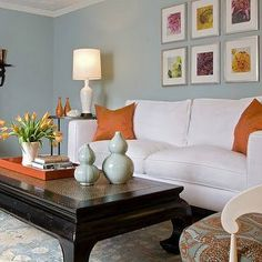 Chic gray living room features a gray sectional draped in an orange Hermes Avalon Blanket and lined with pumpkin orange velvet pillows facing a light grey ottoman as coffee table. Description from decorpad.com. I searched for this on bing.com/images