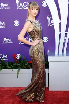 Academy Of Country Music's Entertainer of the Year Taylor Swift perfected her red carpet look in a glitzy gold Dolce and Gabbana gown at the April 7th ceremony. [Photo Credit: Kyle Rover/Startraks Photo]