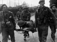 Commandos of No. 4 Commando, 1st Special Service Brigade, use an improvised stretcher to bring one of their casualties back as they advance into Ouistreham, Sword area, 6 June 1944.