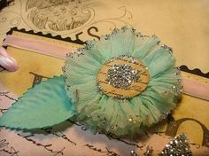 crepe paper flower.1. Using the rolls of party crepe paper-cut one yard then stitch along one edge with a large gathering stitch (by hand or machine).  2. Gather, then tie knots at both ends  3. Glue with a hot glue gun while spiralling onto a circle of paper.  Then glue another circle onto the front.  4. With a pair of pinking sheers, cut around the edges of the flower. You can let this be the finished flower.  5. Or... glitter the edges