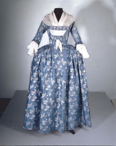 Round gown, c. 1750-1774. Blue silk damask with a pattern of white flowers and fruit vines.