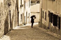 Portugal - Walking with an Umbrella by Jose Antonio Castellanos
