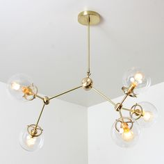 Five vintage-style clear glass Edison bulbs suspend from an industrial-chic, unfinished solid brass frame for a look that is decidedly retro-modern. A dramatic accent for a dining room or entryway.