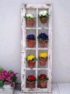 Old windows + hanging pots = garden feature. oh, how cute!! Wendy-I need to know some good shade flowers so I can put this on my porch :)