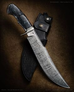 "maker: Sam Lurquin JS website: samuel-lurquin.com Blade Length: 11"" Overall Length: 16 1/2"" Blade & Guard Material: Damascus Handle Material: Stabilized & dyed poplar wood Sheathmaker: Eightball Kustom Leather"