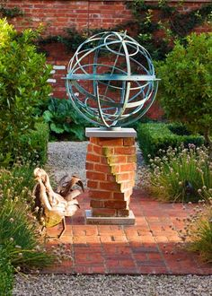 Bronze armillary sphere on an unusual twisted brick plinth  - it would also be cool as a base for a sundial