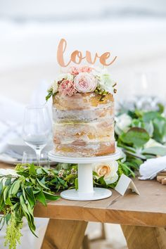 "Naked cake for beach wedding with rose gold ""Love"" topper and fresh pink flowers 