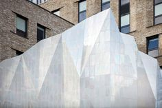 """""""The residential extension complements the hall's Portland stone and weathered brick, in a pale brick which ties the new and historic together,"""" Jestico + Whiles told Dezeen. """"The roof-top pavilion's coloured, fritted glass with anodised fins creates reflections and shadows."""""""