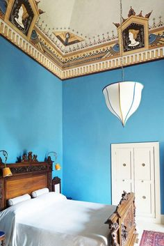 Bedroom with frescos on the ceiling, a pendant light, and electric blue walls