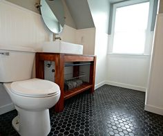 A black hex-tiled bathroom with gray walls and white bead-board wainscoting is warmed up by a DIY wooden vanity.