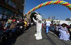 Hands reach out to touch a person dressed as the Easter Bunny as people attend the Los Angeles Mission's Good Friday event on Skid Row on March 29, 2013 in Los Angeles, California. Celebrities and volunteers joined together in giving something back to this community of the homeless, among the largest in the US. AFP PHOTO/Frederic J. BROWN