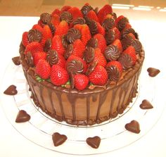 2-layer 10-inch round cake with fresh red strawberries on top with swirl chocolate candies in between strawberries with chocolate dripping down sides...