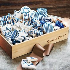 Celebrate the festival of lights with chic sweets for all to share! Filled to the brim with festive blue and white indulgences, Shalom Hanukkah Sweets includes chocolate drizzled popcorn, white chocolate covered pretzels, chocolate drops, chocolate covered almonds, chocolate caramel squares and ten frosted cookies decorated with fun star and drizzle designs. All contents are certified Kosher and come gift wrapped together in a hand crafted wood crate with ribbon.