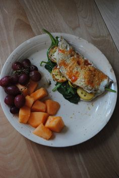 breakfast  egg white omelet filled with raw baby spinach, grilled pattypan squash, pesto, and nooch, topped with hot sauce. red grapes and cantaloupe.