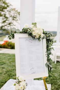 Elegant white garland topped seating chart: http://www.stylemepretty.com/maryland-weddings/baltimore/2016/03/24/classic-elegant-maryland-horse-farm-wedding/ | Photography: Shannon Michele - http://shannonmichelephotography.com/