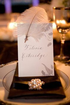 Elegant Gatsby-inspired place setting with a white feather and pearls #wedding #gatsby #placesetting #artdeco #tablescape