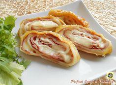 Il rotolo di pasta sfoglia con prosciutto e formaggio è ottimo da servire negli antipasti, da asporto, o per un pranzo o una cena informale con un contorno.