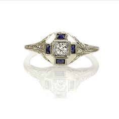 Art Deco Engagement Ring  US$915  Stock Number: VR0414-05  Bordered by four synthetic sapphires set into the octagonal crown, an Old European cut diamond weighs 0.10 cts and has been assessed in the setting as E color and VS clarity. Embellished with a filigree gallery and scroll engraving on the shoulders, this ring is a vintage original c. 1920. 18k white gold. Size 6. Resizing may be possible, Please inquire.