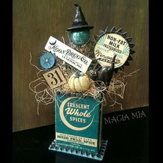 My Halloween Creation using Vintage & Handmade elements: Vintage cardboard Crescent Spice box, Moon Drug Co. label, milk bottle cap, black cat cupcake topper, mercury glass ball, silver lametta tinsel, silver mercury beads, Bingo marker, & Bingo square 31 and 13. Handmade witch hat and pumpkin with Paperclay + black Desden trim, turquoise & silver glass glitter, and cream sisal filler.