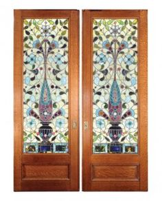 "ONE PAIR OF STAINED GLASS POCKET DOORS, C. 1900 :Made in the USA in the early 20th century, these pocket doors were salvaged from a Brooklyn brownstone. The doors are constructed of quarter sawn oak with stained glass in a floral motif. The stained glass composition is set up in a delightful ombre ranging from a light yellow green to a deep purple. Restored. H 105.5"" x W 34.5"""
